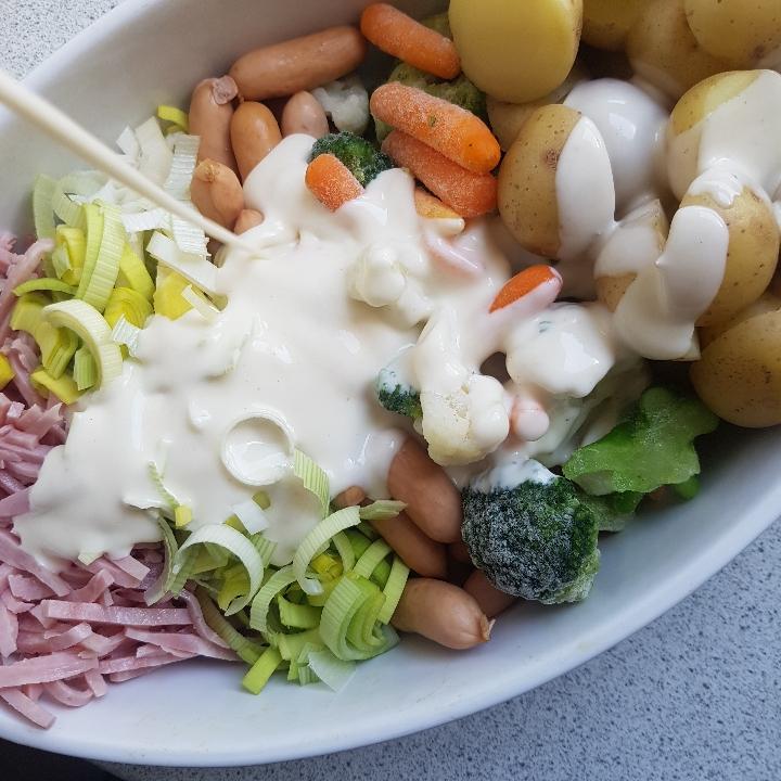 Kartoffelbake med skinke og pølser.