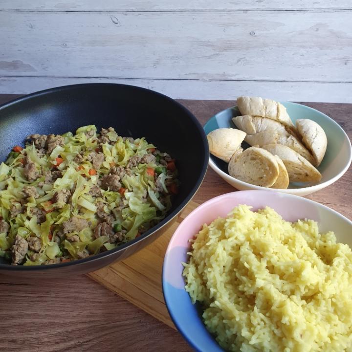 Stegt spidskål med karry og hakket svinekød serveret med karryris